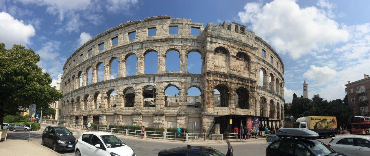 Pano of the Arena set on the busy port side street in Pula