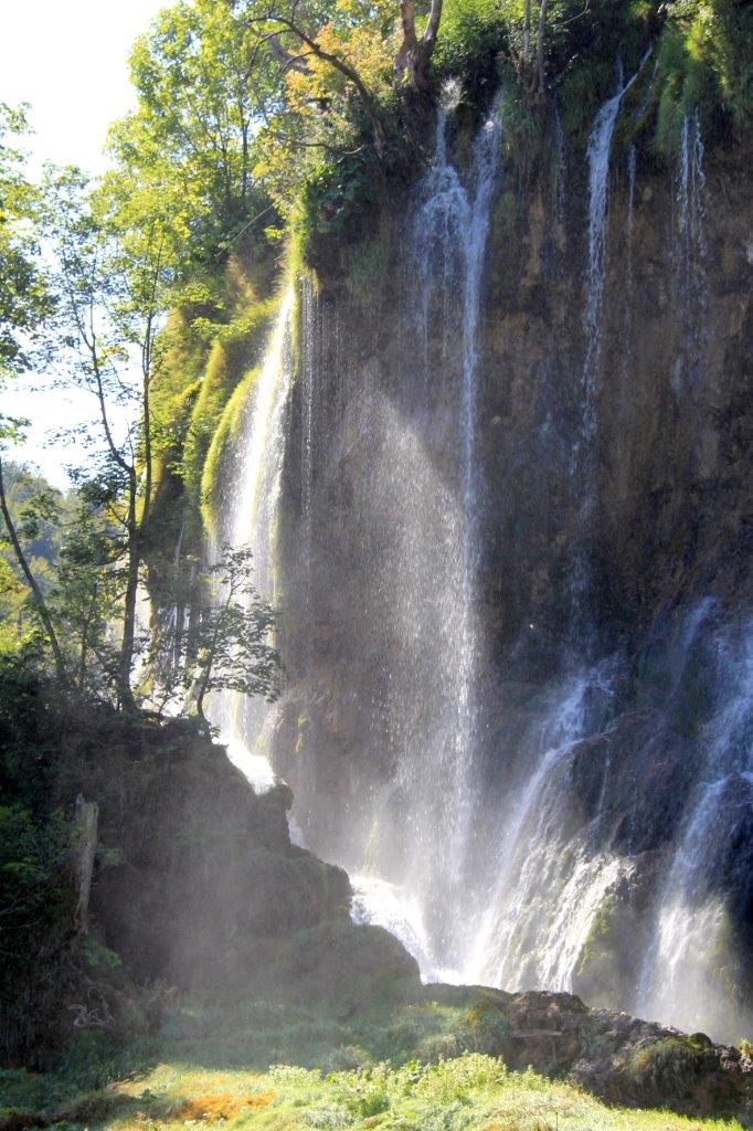 Morning light catches the water as it cascades over the falls at Plitvice