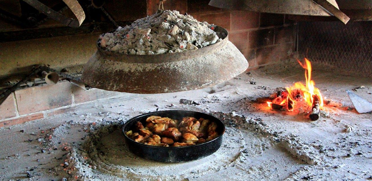 A dome or bell is placed over top of the dish and covered with coals